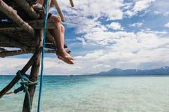 年轻人放松和坐海在夏天海滩风景的海滩码头边缘  免版税库存图片