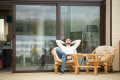 年轻人放松的坐大阳台椅子,呼吸的新鲜空气 库存图片