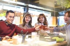年轻人敬酒和吃在餐馆的朋友 免版税库存照片