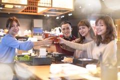 年轻人敬酒和吃在餐馆的朋友 库存照片