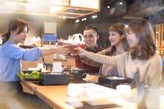 年轻人敬酒和吃在餐馆的朋友 库存图片