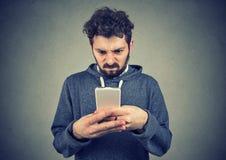年轻人是藏品的智能手机生气与短信 免版税图库摄影