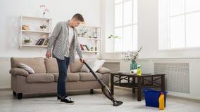 年轻人有吸尘器的清洁房子 免版税库存照片