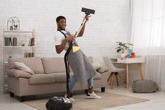 年轻人有吸尘器的清洁房子 库存图片