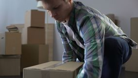 年轻人有材料的包装盒,移动从公寓,租合同的末端 股票视频