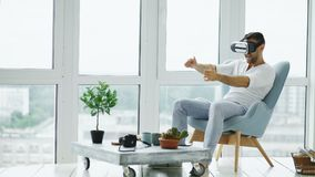 年轻人有演奏VR的经验赛跑比赛的计算机使用虚拟现实耳机在椅子坐阳台 免版税库存图片