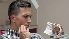 年轻人有牙痛,坐在牙齿椅子在诊所 股票录像