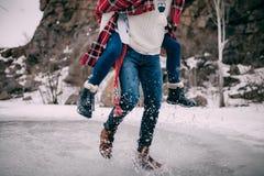 年轻人横跨熔化水水坑运载他的女朋友与飞溅 免版税库存照片