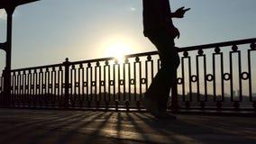年轻人步行和舞蹈在一座现代桥梁在日落在夏天 股票视频