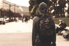 年轻人步行沿着向下一个大城市的街道 免版税库存图片