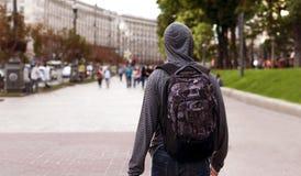 年轻人步行沿着向下一个大城市的街道 库存照片