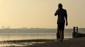 年轻人步行,当发表演讲关于他的机动性在Dnipro在日落时 股票录像