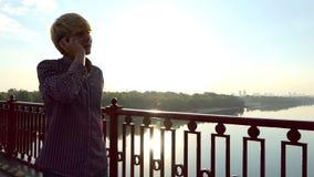 年轻人沿桥梁走并且拔出他的机动性在日落在Slo Mo 股票视频