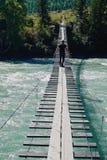 年轻人沿横跨一条山河Katun的一座吊桥走在早期的秋天 免版税图库摄影