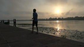 年轻人沿Dnipro河岸愉快地努力去做在日落在Slo Mo 影视素材