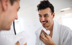 年轻人洗涤物面孔在卫生间里早晨,每日惯例 免版税库存图片