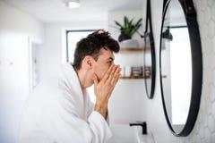 年轻人洗涤物面孔在卫生间里早晨,每日惯例 库存图片