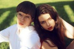 年轻人浪漫夫妇草的在公园 放松在绿草的愉快的夫妇 ?? 有红色嘴唇的一个女孩 ?? 免版税库存图片