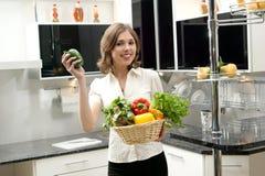 年轻人深色的藏品蔬菜在厨房里 免版税库存图片