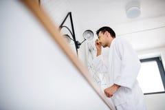 年轻人清洗的面孔在卫生间里早晨,每日惯例 库存照片
