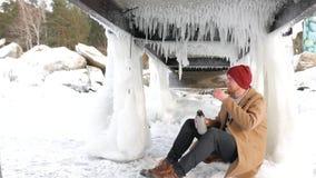 年轻人渔夫与热水瓶坐湖和饮用的茶 股票视频