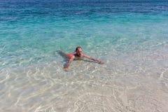 年轻人游泳在海洋在巴厘岛浇灌 免版税库存照片
