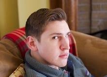 年轻人特写镜头坐看照相机的长沙发 库存照片