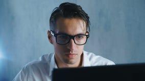 年轻人特写镜头玻璃工作的在使用计算机的办公室 商人饮用的咖啡或茶和工作在 股票录像