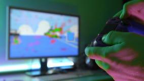 年轻人特写镜头递打在赌博控制台的电子游戏在宽银幕的电视前面 股票视频