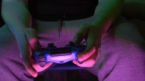 年轻人特写镜头递打在赌博控制台的电子游戏在宽银幕的电视前面 股票录像