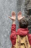 年轻人用手被举往水瀑布  库存图片