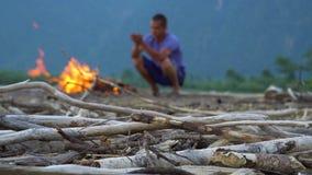 年轻人由在一个沙滩的火温暖自己 股票录像