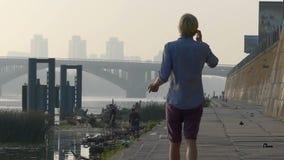 年轻人由机动性在河岸讲话,姿势示意,在夏天在Slo Mo 股票视频