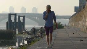 年轻人由机动性,步行,微笑讲话,在河岸在Slo Mo 股票视频