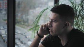 年轻人由电话讲话 在netbook的自由职业者工作在现代coworking 在遥远的工作的程序员 成功的人民 股票录像