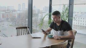 年轻人由电话讲话 在netbook的自由职业者工作在现代coworking 在遥远的工作的程序员 成功的人民 影视素材