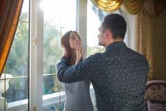 年轻人由窗口与夫妇争吵结婚在一个现代房子里 图库摄影
