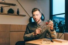 年轻人画象有杯的科涅克白兰地和雪茄在坐在桌上的手上 免版税库存照片