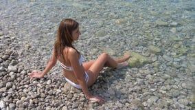 年轻人白色比基尼泳装的被晒黑的妇女坐天蓝色的海的有卵石花纹的岸 股票录像