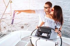 年轻人的好的图片一起站立和朝左边看 他指向用手 她握她的在船舵的手 图库摄影