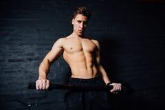 年轻人的画象完全符合人锻炼在健身房锤子 肌肉运动 库存照片
