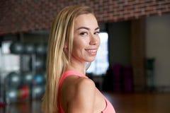 年轻人的画象白剥皮了在健身房的背景的微笑的女孩体育教练 友好的微笑和运动修造 库存图片