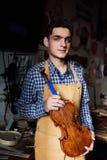年轻人的画象luthier与一把被手工造的小提琴在他的有工具的车间 库存照片