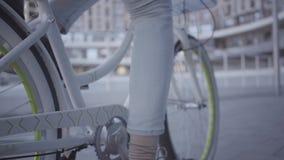 年轻人的脚骑他的在城市关闭的浅兰的牛仔裤的自行车  英俊的城市居民休闲  活动家 股票录像