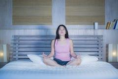 年轻人相当亚裔中国妇女在家放松卧室的20s或30s坐在莲花瑜伽位置的床在凝思和放松 库存照片