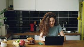 年轻人相当卷曲白种人妇女单独在运作好的宽敞厨房的idoors的桌上坐听的膝上型计算机 影视素材