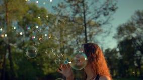 年轻人相当女性制造的肥皂泡 与橙色叶子的美丽的树 股票视频
