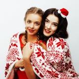 年轻人相当愉快微笑白肤金发和深色的妇女女朋友在圣诞老人红色帽子的圣诞节和假日装饰 免版税库存图片