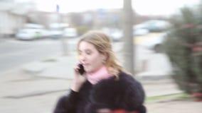 年轻人相当白肤金发的女孩谈话在智能手机 股票录像
