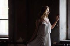 年轻人相当逗人喜爱的女孩室内夏天画象  摆在木内阁里面的两个童话窗口,伤痕o旁边的美丽的妇女 免版税库存图片